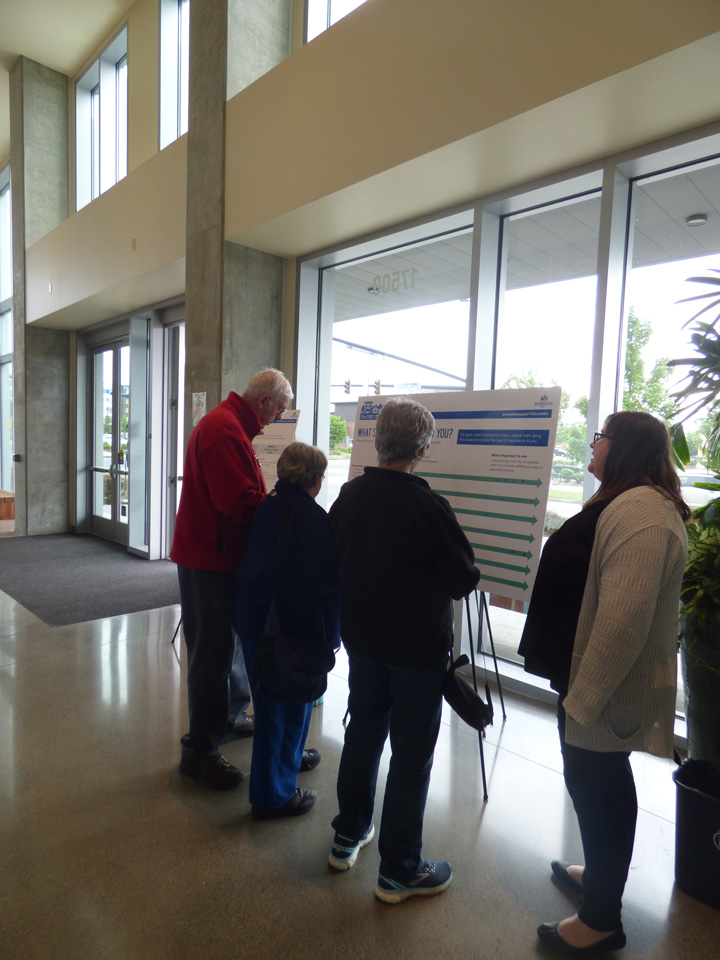 Four people stand in front of an informational board inside Shoreline City Hall.